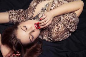 Glamor portrait of beautiful woman lying on black bed