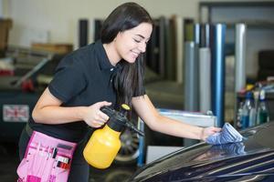 trabajador de limpieza de coche con un paño y una botella de spray foto