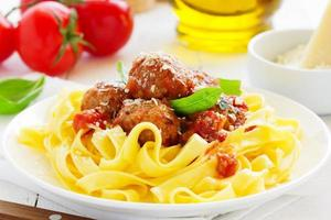 Egg tagliatelle with meatballs in tomato sauce. photo