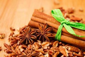 Cinnamon sticks, anise and pecan nuts on wooden tabletop