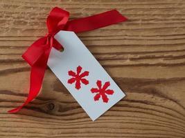 navidad, etiqueta de regalo, impreso, cinta roja, madera de fondo