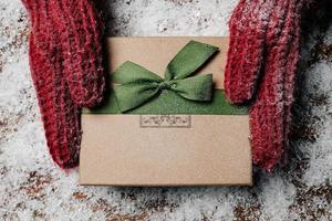 mãos segurando um presente de natal com decoração rústica
