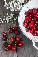 Cerezas maduras orgánicas limpias frescas en un colador foto