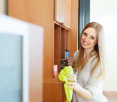 feliz chica rubia de pelo largo limpiando el polvo foto
