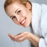 Young woman washing face photo