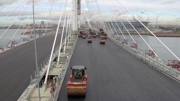 Aerial shot Trucked paver and compactors paving asphalt on a modern cable-stayed bridge on a cityscape video