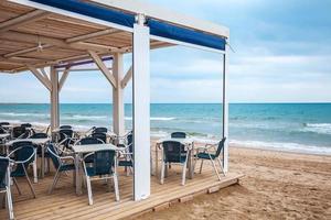 Interior de la barra junto al mar con suelo de madera y sillones de metal