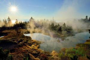 sunrise, steaming geysers and a lake photo