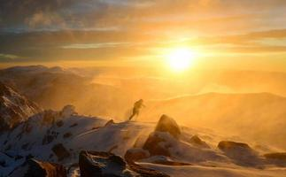 Climber fights with bad weather in the winter mountains photo