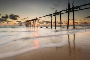 línea de pestañas de olas del mar en la playa con el viejo puente foto