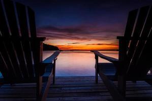 sillas de playa en un puente de madera con puesta de sol