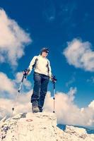 Young woman standing on top of a mountain photo