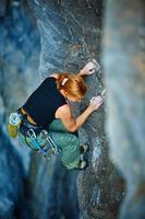 Rock climber climbing up a cliff photo