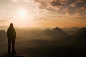 Hiker stand on rock  and watch to  miracle of nature photo