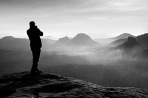 Professional photographer takes photos with big camera on rock