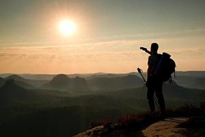 Tall backpacker with poles in hand. Sunny daybreak in mountains. photo
