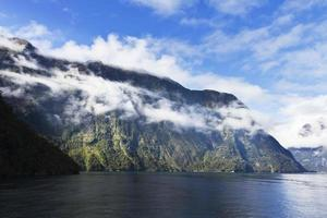 Grassy mountain above water on foggy Milford Sound.