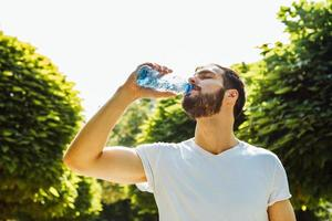 adult man drinking water from a bottle outside