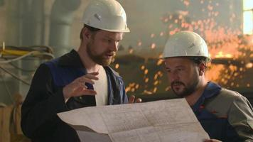 portrait of two engineers explore and discuss project in heavy industry factory. welding video