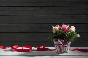Rosas en canasta con cinta, fondo de madera foto