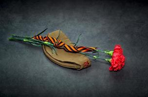 Carnation flowers, George Ribbon and military garrison cap photo