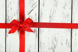 Red ribbon with bow on white wooden background photo