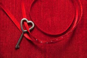 Heart shaped key and ribbon on red velvet
