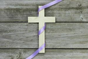 Wooden cross with purple ribbon on wood background photo
