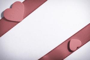 cinta roja y símbolo del amor del corazón en blanco foto