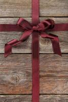 Burgundy ribbon with bow on grey wooden background photo