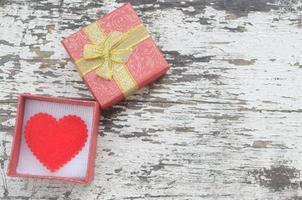 Corazón rojo en caja de regalo en madera grunge