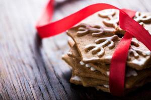 Gingerbread cookies with red ribbon on wooden background
