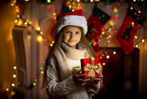 portrait of smiling girl opening sparkling gift box at Christmas