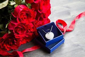 día de san valentín rosas rojas y caja de regalo. foto