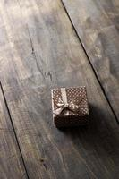 Gift box with ribbon ornament on wooden background. photo