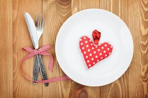 Valentine's Day toy heart over plate with silverware