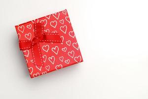 Red gift box with bow and painted hearts isolated top