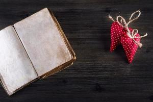 Valentines day. Red cloth handmade hearts and old open book photo