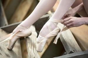 Ballerina tying the ribbon on his white pointe