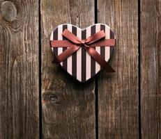 Heart-shaped Valentines Day gift box on wooden plates. photo