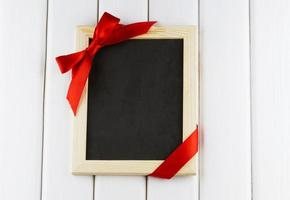 Empty blackboard decorated red bow and ribbon