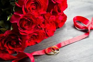 valentine's day Red roses and wedding ring  a wooden background