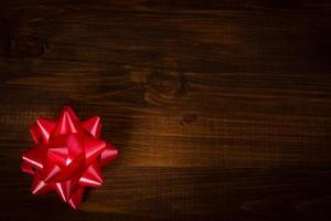 Red bow on wooden brown planks