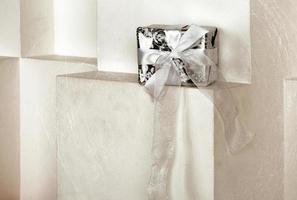 Gift box standing on a white shelf. photo