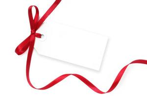 A blank, white tag with a flowing red ribbon tied on it
