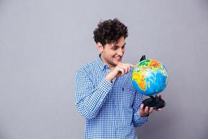 Man pointing finger on globe