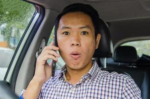 Shocked man talking on the phone in the car