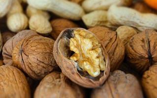 Broken walnut over nut and peanuts