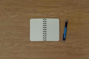 Vista superior del bloc de notas y bolígrafo sobre mesa de madera