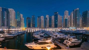puerto deportivo de dubai en timelapse de la noche a la hora azul con yates